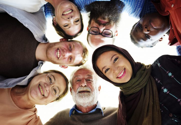 Photograph of a circle of faces illustrating how people are at the heart of the Social Context approach.
