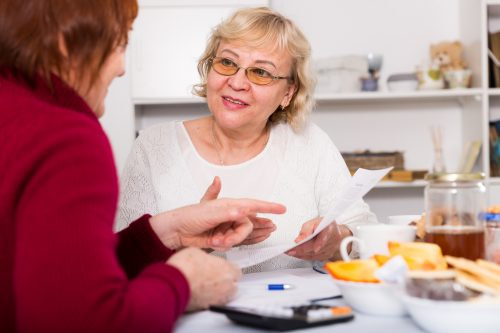 Photograph of two women sitting at a kitchen table and talking, illustrating the Social Context approach to human-centred design research.